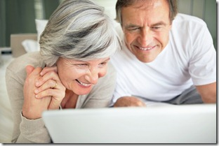 Happy retired couple using a laptop together