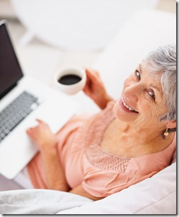 Happy old woman drinking coffee and using laptop